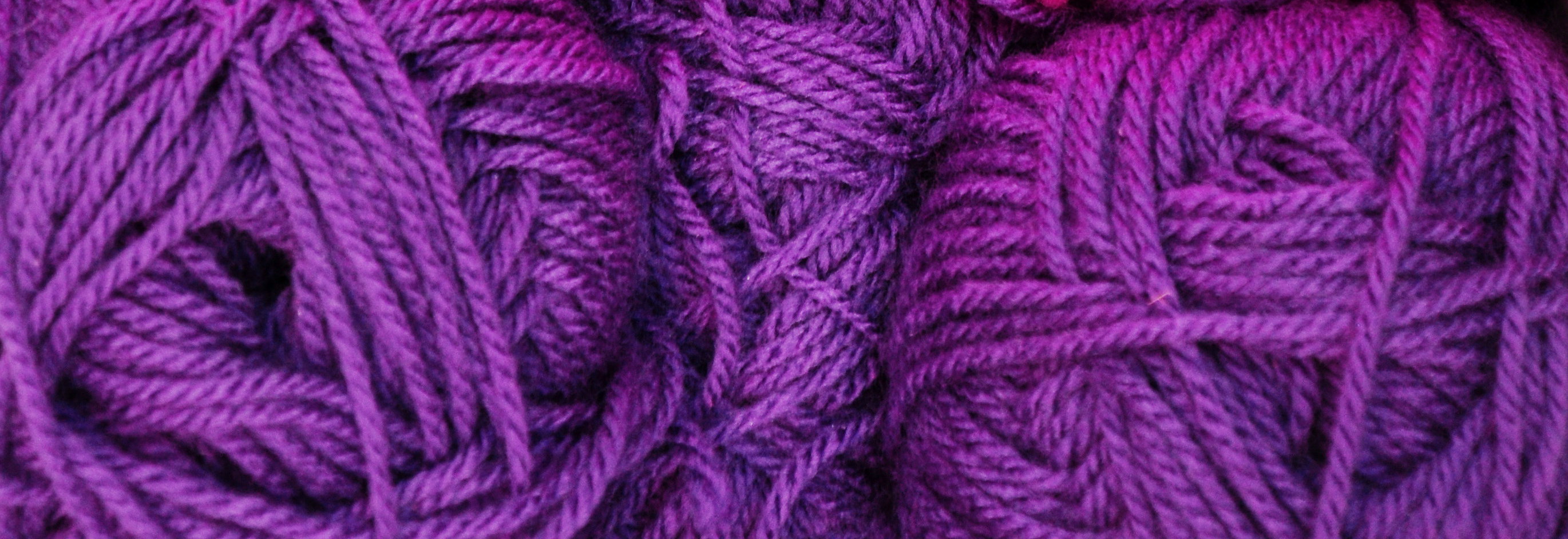 Photo shows close-up shot of balls of purple yarn.